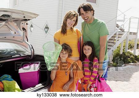 images parents et deux enfants devant a maison pr s leur voiture pr t aller les. Black Bedroom Furniture Sets. Home Design Ideas