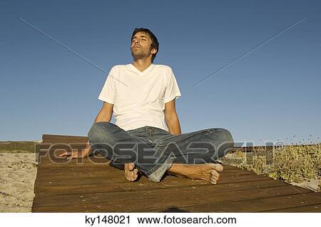 Man Sitting Cross Legged Side View Young man sitting cross-legged