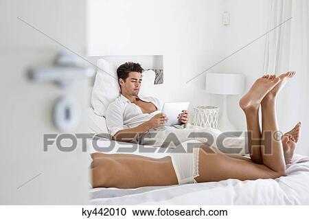 banques de photographies femme dans lingerie mensonge lit et lecture homme a tablette. Black Bedroom Furniture Sets. Home Design Ideas