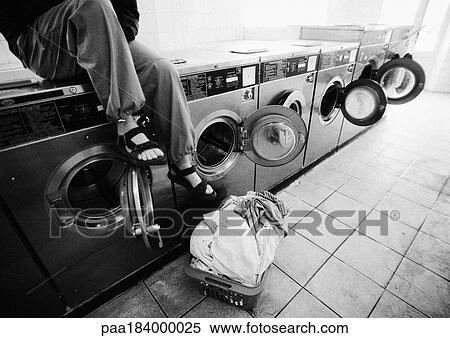banque d 39 image s ance personne sur machine laver dans laundrymat basse section b w. Black Bedroom Furniture Sets. Home Design Ideas