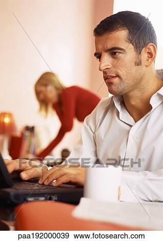 Stock Photograph of Man working on computer, woman in background ...