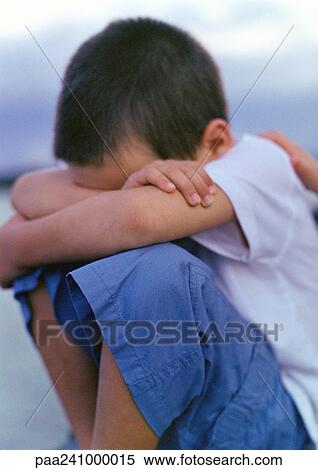 Stock Image Of Boy Sitting With Knees Up And Arms Folded