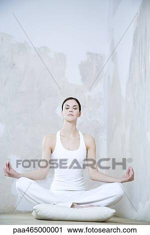 Young Woman Sitting In Lotus Position Enjoying Meditating