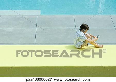 Foto chico que sienta al lado de piscina utilizar for Auriculares para piscina