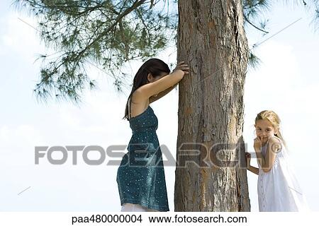 Stock Photo of Two young friends playing hide-and-seek ...