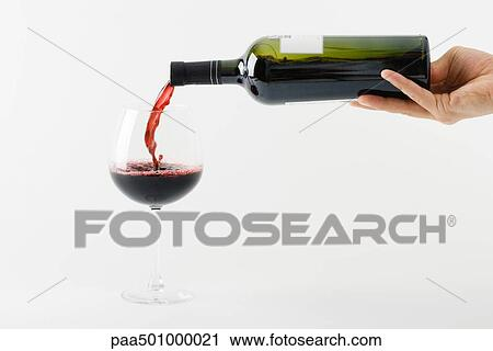 Stock Photography of Hand pouring red wine into glass ...