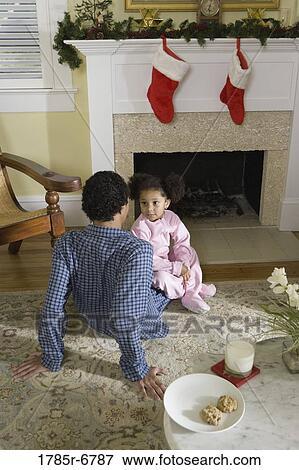 Beeld aanzicht van broer en zus zittende door openhaard verfraaide voor xmas wachten - Tapijt tienerjongen ...