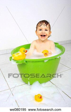 stock image of baby sitting in tub having a bath with lots of soap foam and yellow plastic. Black Bedroom Furniture Sets. Home Design Ideas