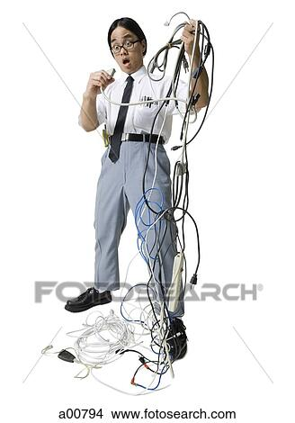 mess office stock photo of office worker with tangled mess of wires a00794