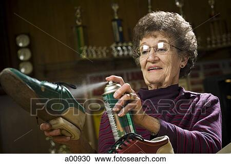 Stock Photography of Female bowling attendant spraying bowling ...