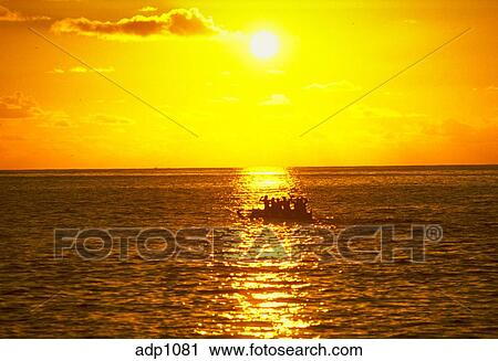 Stock Photography of Outrigger canoe on the ocean at sunset, with ...