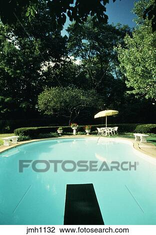 Stock Photo Of Swimming Pool With Diving Board At Private Residence Picnic Table And Umbrella