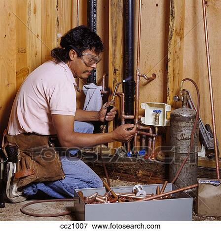Picture Of A Latino Plumber Uses An Acetylene Torch To