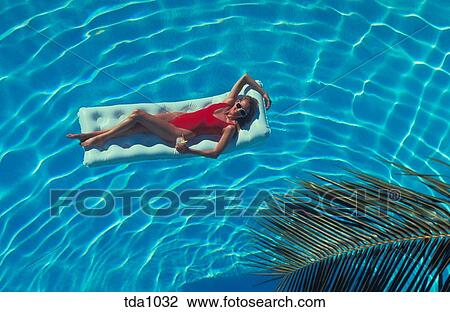 Stock photo of a young woman in a red bathing suit holding How to make swimming pool water drinkable