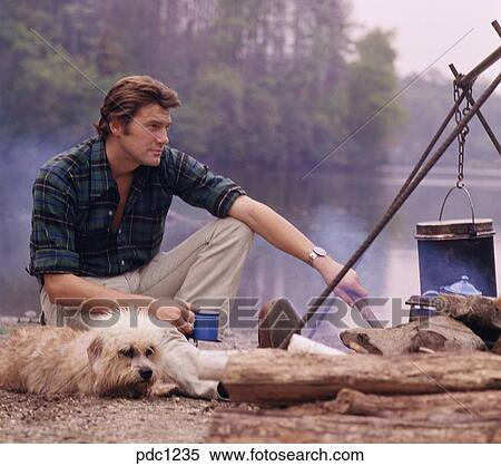 Stock Image of Rugged outdoors man sitting at his campsite