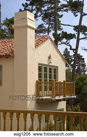Exterior Of A SPANISH STYLE CALIFORNIA LUXURY HOME Showing ROOF And  Upstairs BALCONY With WOODEN RAILING