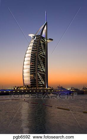 Stock photo of dubai evening view over marina at jumeirah for Sail shaped hotel dubai