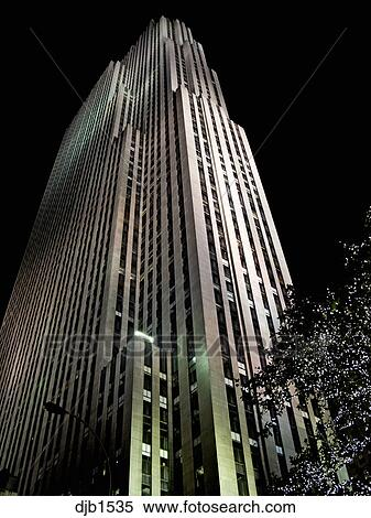 Rockefeller Center building in New York City at night looking straight up  and lighted with spot lights and trees with small lights.