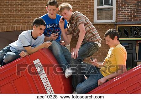 Pictures Of 4 Teenage Boys Using Their Cell Phones