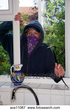 Picture - Teenage boy using a crowbar to break into a house wearing a hoodie and