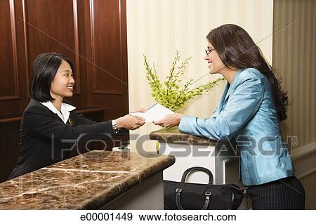 Stock Photograph Woman Hotel Desk Clerk Handing Paperwork To Guest Fotosearch Search