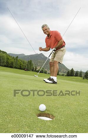 Picture Of Man Sinking Putt On Golf Green E00009147