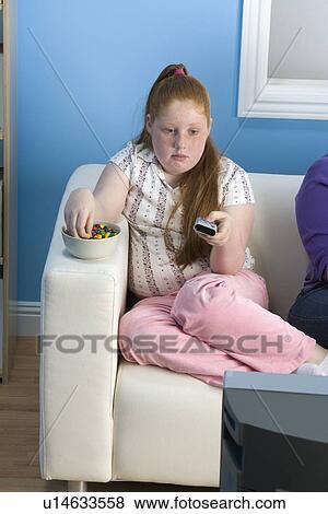 bilder bergewichtige m dchen aufpassendes fernsehen auf sofa u14633558 suche stockfotos. Black Bedroom Furniture Sets. Home Design Ideas