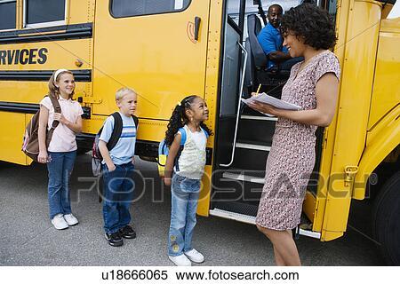 Stock image of teacher loading elementary students on school bus stock image teacher loading elementary students on school bus fotosearch search stock photos voltagebd Choice Image