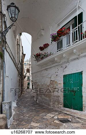 bild stra e in ostuni mit typisch wei stuck w nde stein pflastern schmiedeeisen. Black Bedroom Furniture Sets. Home Design Ideas
