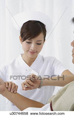 Pictures of Young nurse taking pulse for the patient and ...