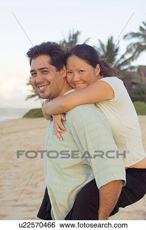 Stock Images Of Multiracial Couple Embracing On Hawaiian