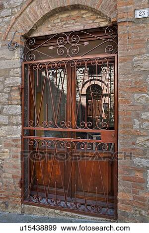 Arched glass and wooden panelled door with wrought iron gate in front reflecting another arched door in the glass with surrounding stone wall ... & Stock Photograph of Arched glass and wooden panelled door with ...