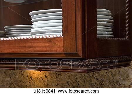 KITCHEN: Close Up Of Edge Of Glass Kitchen Cabinet, Rope Molding, White  Plates Stacked, Glass Is On Front And Sides Of Cabinet