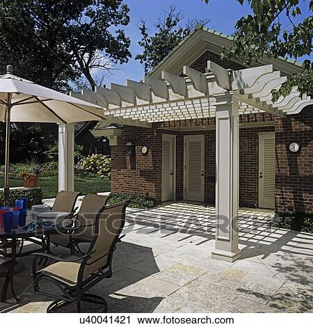 PATIOS: Patio Eating Area Off Red Brick Pool House With White Wood Portico.  Iowa Limestone, Umbrella Glass Top Table With Chairs, Lawn Off To The Left.