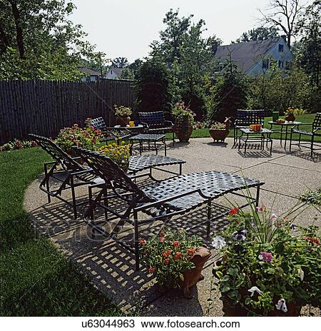 Stock Photo   PATIOS: Rounded Concrete Patio With Pebbles, Black Patio  Furniture, Many