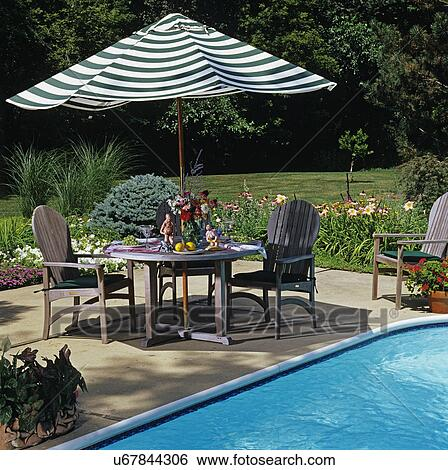 Stock Image   PATIOS: Pool Side Patio, With Flower Border Garden. Table With