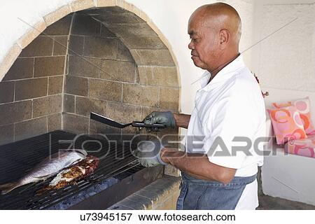 Beeld man het koken vis op binnen grill mykonos griekenland u73945157 zoek stock for Beeldkoken