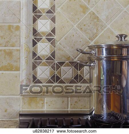 picture tile detail of tumbled marble tile behind commercial kitchen range beige and
