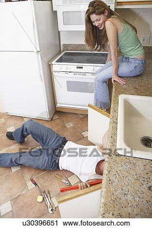 Stock Photography of Young woman watching plumber fixing kitchen ...