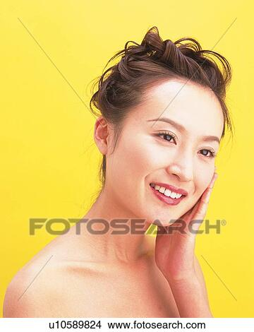Portrait of a Young Adult Woman Holding her Face, Looking Sideways,  Smiling, Side View