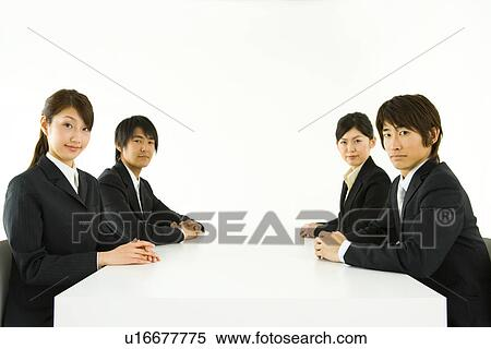 people sitting at table white background. stock image - portrait of four young business people sitting at table, looking camera table white background t