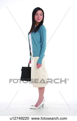 Stock Photography of Young woman standing, carrying ...