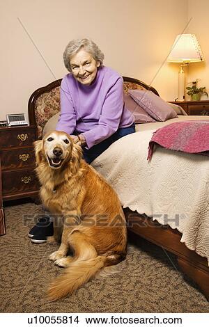 banque de photo personnes ag es caucasien femme et chien dans elle chambre coucher. Black Bedroom Furniture Sets. Home Design Ideas