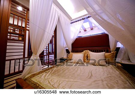 picture modern four poster bed with white curtains at the four corners fotosearch