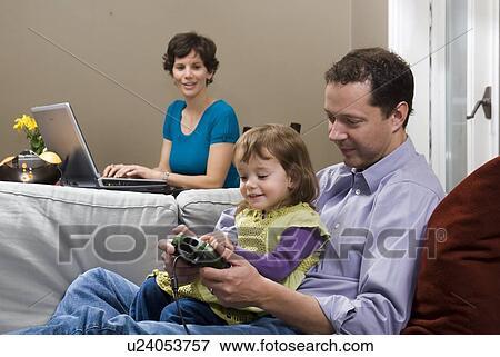 Bild Mann Und Kind Mit Spiele Konsole Auf Sofa Frau Hinter Laptop Benutzend Winnipeg