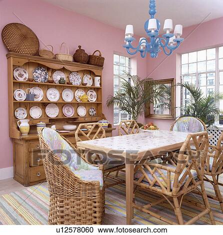 Blue Wood Chandelier Above Table With Wicker And Cane Chairs In Pink Eighties Dining Room Large Pine Dresser