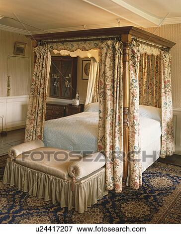 Picture of country bedroom with antique four poster bed with floral curtains and ottoman with - Four poster bed curtains ...