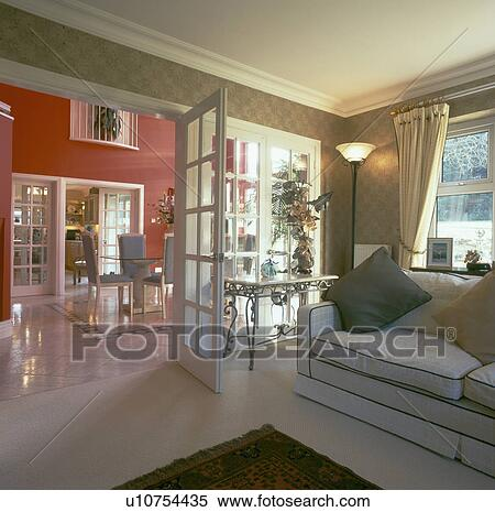 Open Double Glass Doors Between Living Room With Cream Sofa And Red Dining