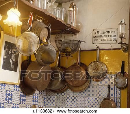 Beeld oud metaal zeefen en koper saucepans op muur boven blue white tegels in - Tegel keuken oud ...