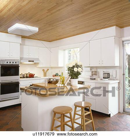 White Kitchen With Wooden Worktops stock photograph of wooden stools and island unit with wood